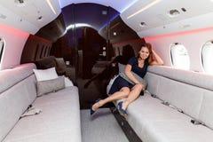 豪华内部的年轻美丽的妇女在企业喷气机 免版税图库摄影