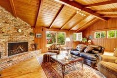 豪华原木小屋房子内部 有壁炉的客厅和 免版税库存图片