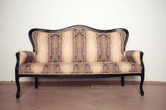 豪华古色古香的velor沙发在一个木地板上站立在墙壁附近 图库摄影