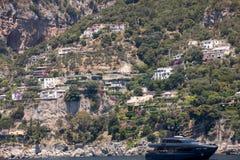 豪华在波西塔诺,褶皱藻属附近crewed在阿马尔菲海岸的马达游艇 库存照片