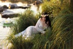 豪华夫人,说谎在湖岸的典雅的长的礼服的  免版税库存照片