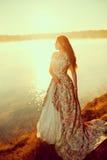 豪华妇女在一件长的葡萄酒礼服的一个森林里在湖附近 库存照片