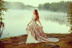 豪华妇女在一件长的葡萄酒礼服的一个森林里在湖附近 库存图片