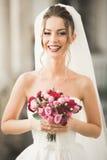 豪华婚礼新娘,摆在和微笑与花束的女孩 免版税库存照片