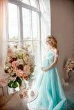 豪华婚礼礼服的时尚怀孕的白肤金发的妇女 婚姻 图库摄影