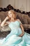 豪华婚礼礼服的时尚怀孕的白肤金发的妇女 婚姻 免版税库存图片