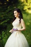 豪华婚礼礼服的美丽的新娘在紫色淡紫色fl 库存照片