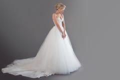 豪华婚礼礼服的迷人的年轻新娘 相当女孩白色 幸福、笑声和微笑的情感,灰色 免版税库存照片