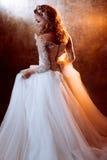 豪华婚礼礼服的,在金黄口气,强光的作用的画象美丽的女孩新娘 免版税图库摄影