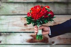 豪华婚礼花束由红色牡丹和玫瑰做成 免版税图库摄影