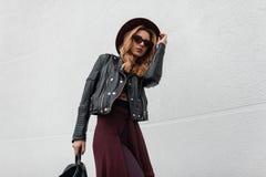 豪华帽子的典雅的年轻行家妇女在一皮夹克的太阳镜在有一个背包的裤子有海角旅行的 库存照片