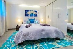豪华床关闭与墙壁艺术在一间现代卧室 免版税库存照片