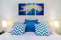 豪华床关闭与墙壁艺术在一间现代卧室 免版税图库摄影