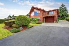 豪华房子外部与木盘区修剪、车库和保管妥当的庭院 免版税库存照片