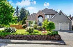 豪华房子外部与砖和房屋板壁修剪和双重车库 免版税库存照片