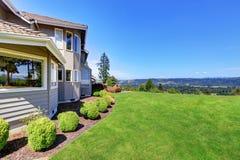 豪华房子外部与草填装了庭院和灌木 免版税库存照片
