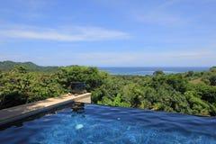 豪华房子的无限水池有雨林和海滩,哥斯达黎加的看法 免版税库存图片