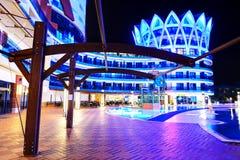 豪华旅馆游泳池和大厦在夜 免版税库存图片