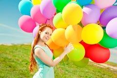 豪华有气球的时尚时髦的妇女在手中在领域 免版税库存图片