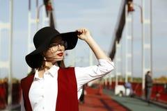 豪华模型室外画象穿红色服装,黑帽会议, s 免版税库存图片