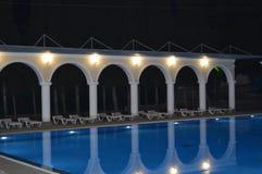 豪华水池的夜视图与专栏和曲拱的,反映在水 免版税图库摄影