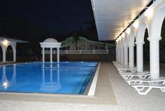 豪华水池的夜视图与专栏和曲拱的,反映在水 库存图片