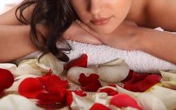 豪华温泉沙龙的妇女在有玫瑰花瓣的竹席子 特写镜头表面纵向妇女 温泉、健康和医治用的概念 库存图片