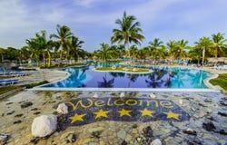 豪华游泳池和旅馆地面华美的邀请的看法在热带庭院里 免版税库存照片