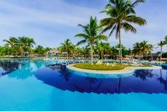 豪华游泳池和旅馆地面邀请的看法在热带庭院里 免版税库存图片
