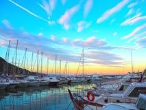 豪华游艇和风船在日落的海口 现代汽船海洋停车处在利古里亚,意大利 免版税库存图片