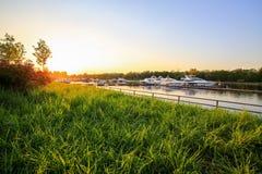 豪华游艇在小游艇船坞靠了码头在五颜六色的日落 停放在码头的现代小船 河岸夏天视图  库存照片