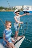 豪华游艇的愉快的逗人喜爱的孩子在口岸的夏天晴天 库存照片
