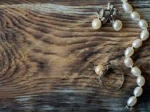 豪华珍珠项链、圆环和珍珠耳环在老木桌上 拷贝空间,关闭 库存照片