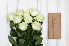豪华白玫瑰和一个当前箱子花束在eco纸在白色木背景 顶视图,平的位置 库存照片