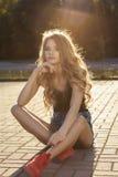 豪华白肤金发的模型在被剥去的牛仔裤短裤和黑色穿戴了 库存照片