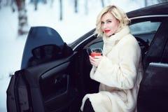 豪华白色皮大衣的美丽的女商人喝热的咖啡的在坐在她的汽车的多雪的冬日 免版税库存照片