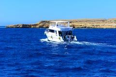 豪华白色马达游艇在反对独特的Ras默罕默德自然的老珊瑚礁蓝天的红海  免版税库存照片