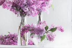 豪华的新鲜的紫色丁香花束在玻璃花瓶的 免版税库存照片