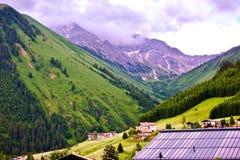 豪华的绿色高山峰顶和谷与瑞士山中的牧人小屋屋顶在前景在Berwang,提洛尔 图库摄影