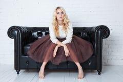 豪华的裙子的典雅的少妇坐长沙发 免版税库存照片