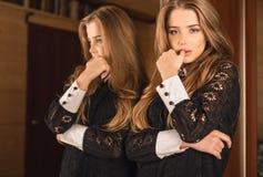 豪华礼服摆在的典雅的年轻秀丽妇女室内反对镜子 免版税库存照片