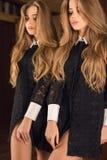 豪华礼服摆在的典雅的年轻秀丽妇女室内反对镜子 库存照片