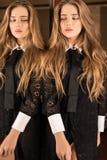 豪华礼服摆在的典雅的年轻秀丽妇女室内反对镜子 图库摄影
