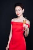 豪华红色礼服的年轻亚裔妇女有杯的闪耀的wi 库存图片