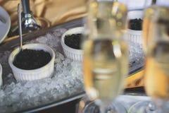 豪华美妙地装饰了承办酒席宴会桌用用黑和红色鱼子酱和不同的食物快餐 图库摄影