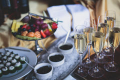 豪华美妙地装饰了承办酒席宴会桌用黑和红色鱼子酱和不同的食物快餐,在党 免版税库存照片
