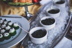 豪华美妙地装饰了承办酒席宴会桌用黑和红色鱼子酱和不同的食物快餐,在党 库存照片