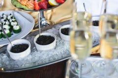 豪华美妙地装饰了承办酒席宴会桌用黑和红色鱼子酱和不同的食物快餐,在党 免版税图库摄影