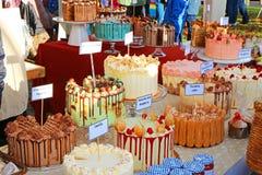 豪华蛋糕待售在市场摊位 库存照片