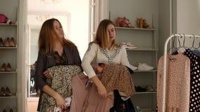 豪华衣裳精品店的两个典雅的白肤金发的姐妹拿着与选上的衣裳时髦女衬衫的挂衣架,愉快 影视素材